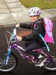 girl on bike with backpack and helmet
