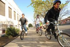 3 kids on bikes on the sidewalk