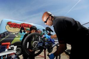 person fixing bike in front of the bikemobile van
