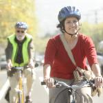 Woman riding bike with helmet and smiling