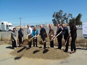nine people in suits digging a hole at a groundbreaking event