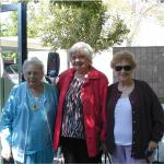 three elderly women standing in the shade with trees behind them