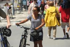 woman walking her bike on a crowded sidewalk