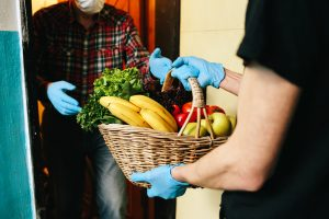 COVID-10 volunteer in a medical mask and gloves passes a basket of food to senior citizen in mask.