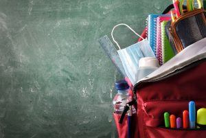 Backpack with school supplies, including mask and sanitizer, with green blackboard in background